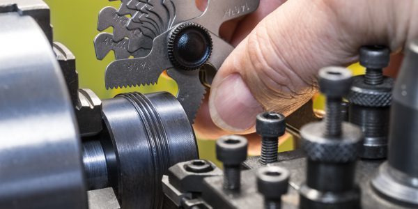Detail of a machinist's hand with the set of threaded gauges. Threading by a steel tool bit on a lathe. Workpiece, holder. Idea of machining, metalworking, engineering