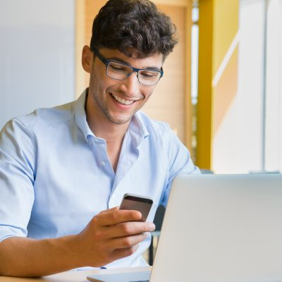 Closeup shot of a young man typing a text on mobile phone. Guy holding a modern smartphone and writing a phone message. Smiling young businessman looking at cellphone with laptop on table at coffee bar.