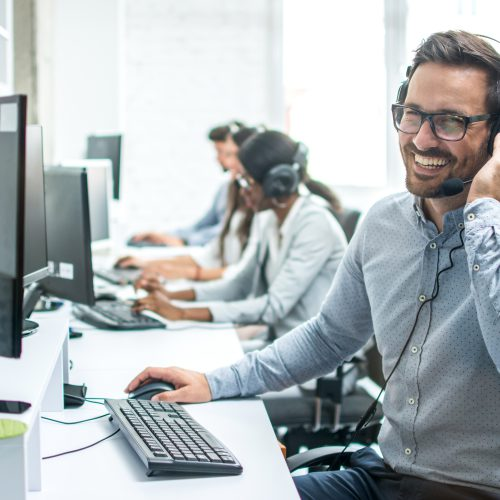 Smiling handsome customer support operator with headset working in call center.